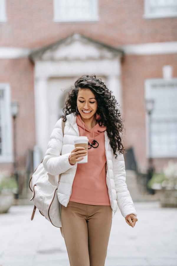 happy ethnic woman walking with coffee cup in street