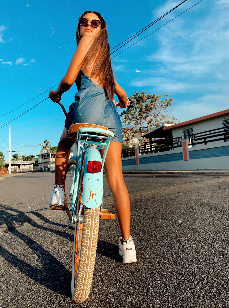 back view photo of woman in blue dress and sunglasses sitting on blue bicycle looking back