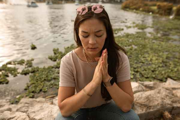 stressed woman sitting with eyes closed on lake shore