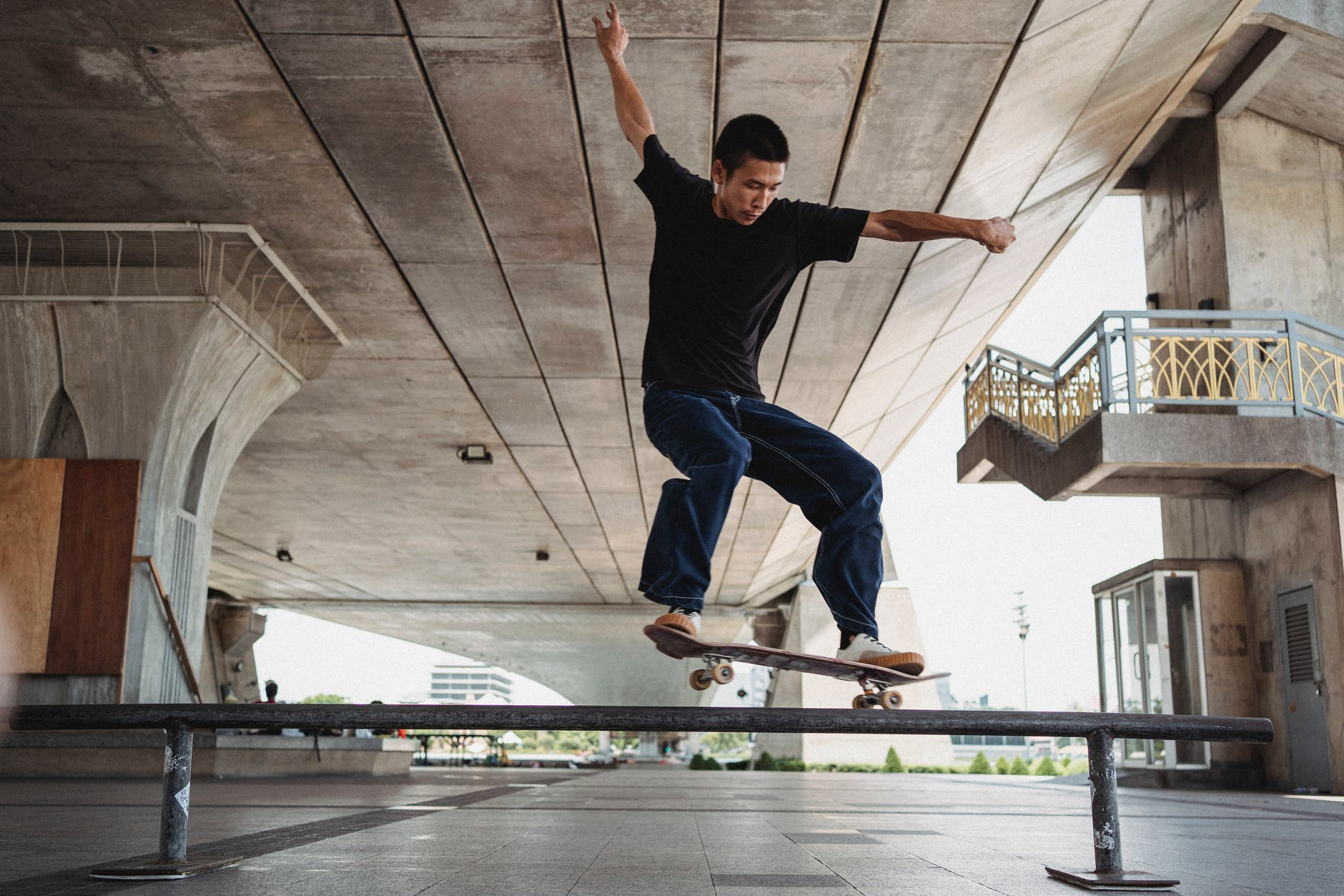 active asian man performing trick on railing