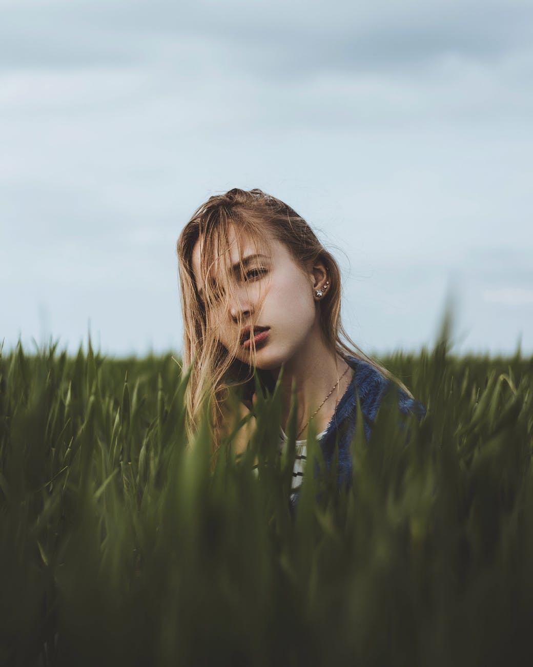 tranquil woman sitting in tall grass